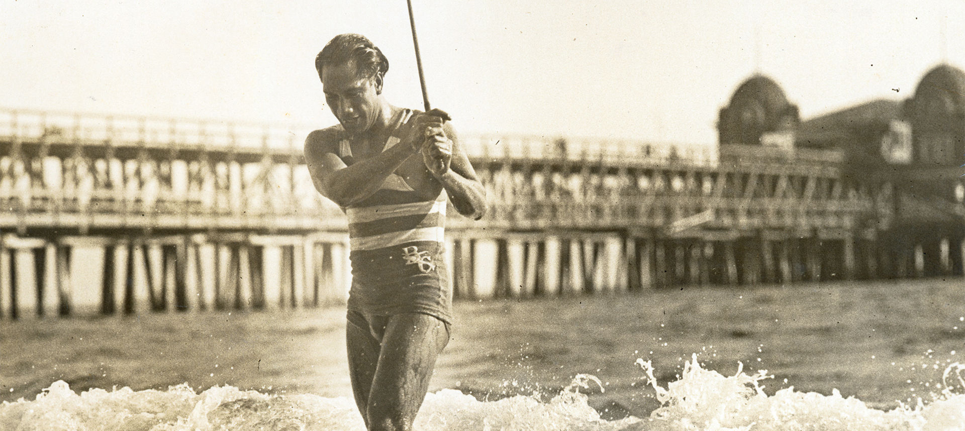 Duke exiting ocean with stick in hand