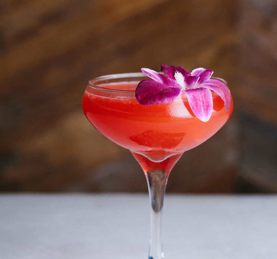 pink cocktail garnished with flower